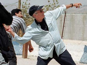Edward Said throws a                     stone across the border from Lebanon to Israel on 3                     July 2000.